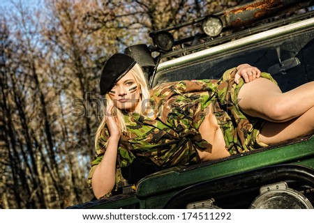 Beautiful girl on camouflage outfit lying top of the off-road vehicle bonnet - stock photo
