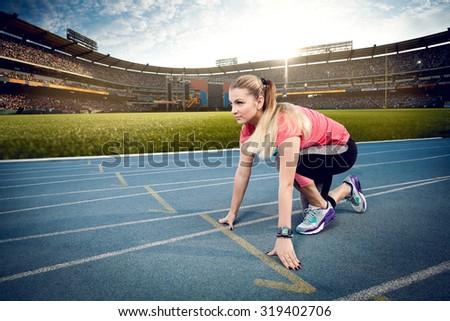 Beautiful girl on stadium is ready to run - stock photo
