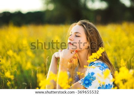 Beautiful girl on the flowers field Beautiful blonde woman in the flowers field on sunset  Soft focus - stock photo