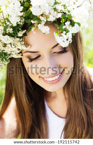Beautiful girl on the nature wearing wreath of white flowers - stock photo