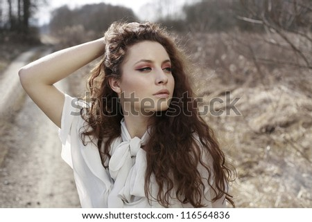 Beautiful girl on the road in nature with long curly red hair - stock photo