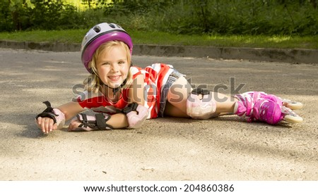 beautiful girl on the rollers fell  and smiling - stock photo