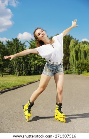 Beautiful girl on the yellow roller  in the park - stock photo