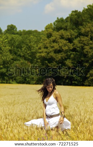 Beautiful girl on wheat field during a hot summer day. Full of colors, warm tones, freshness and serenity. She is wearing a white dress and enjoying some free time walking under the nice sunlight. - stock photo
