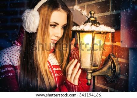 beautiful girl on winter street with lamp - stock photo