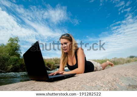 Beautiful girl outdoors with laptop lying on a rock