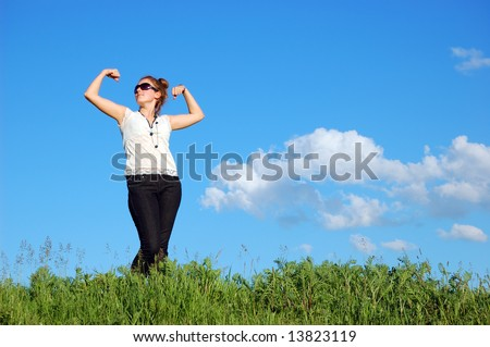 Beautiful girl over a blue sky with clouds - stock photo