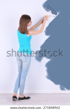 Beautiful girl paints wall in room - stock photo