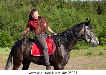 Beautiful girl patting a horse on the rump - stock photo