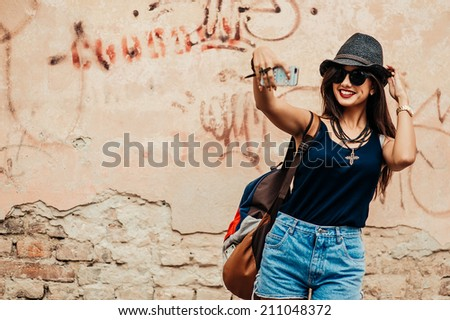 beautiful girl photographed themselves on the background wall graffiti - stock photo