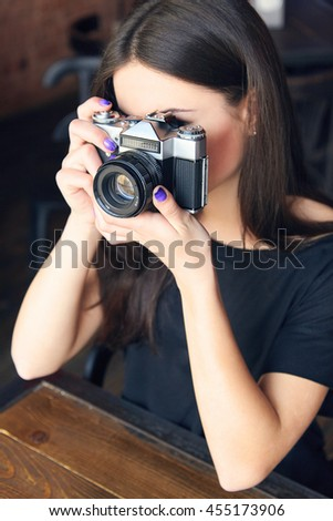 Beautiful girl photographer is holding old analog film camera in her hands. Young woman in black t-shirt looking at viewfinder and making photo in cafe.