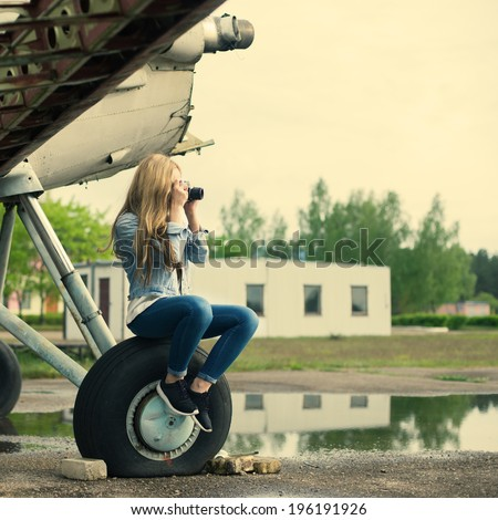 Beautiful girl photographer sitting on the wheel of an old aircraft - stock photo