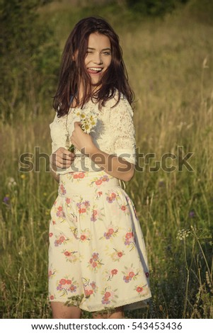 Beautiful girl picking flowers on field