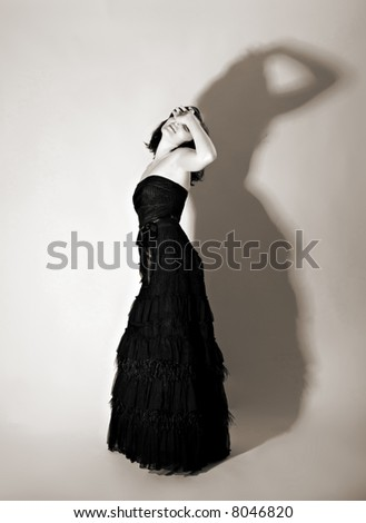Beautiful girl playing role of a diva, toned sepia - stock photo