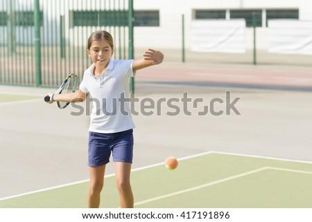 Beautiful girl playing tennis on tennis court - stock photo