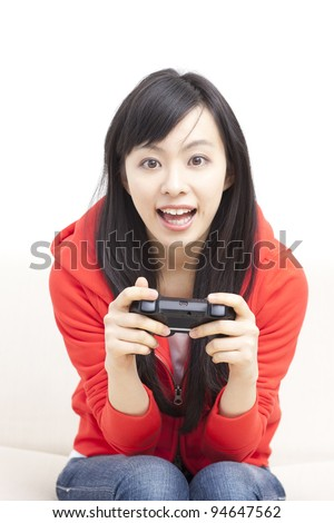 beautiful girl playing video game on sofa - stock photo