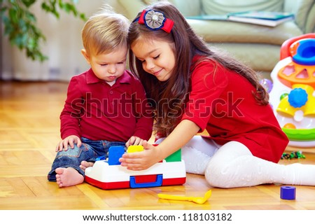 beautiful girl playing with little brother at home - stock photo