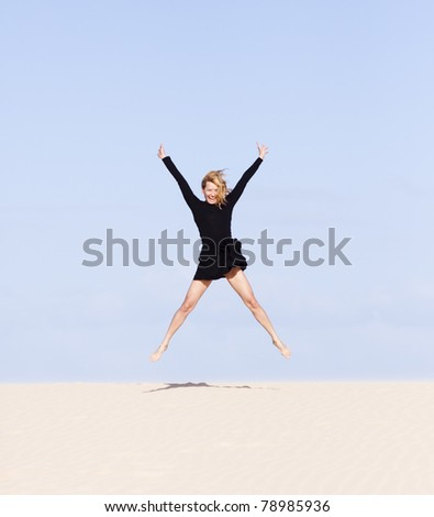 Beautiful girl playing with the sand on the dune. - stock photo
