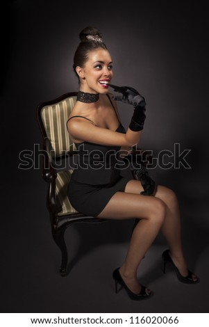 Beautiful girl  portrait in retro style. Glamorous woman in black outfit takes off glove with hers teeth