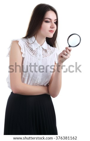 Beautiful girl portrait looking through magnifier