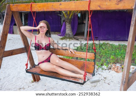 Beautiful girl poses on the beach - stock photo