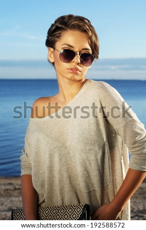 beautiful girl posing against blue sea and sky and looking at you. Summer outdoor fashion portrait. - stock photo