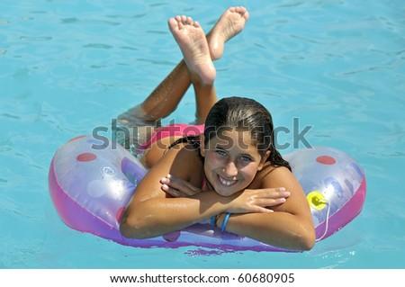 Beautiful girl posing in a swimming pool - stock photo