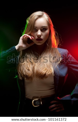 Beautiful girl posing in front of shining colored creative lighting background - stock photo