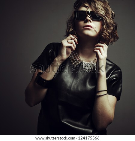 beautiful girl posing in studio in leather dress and sunglasses - stock photo