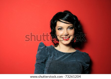 Beautiful girl posing in studio on red background - stock photo