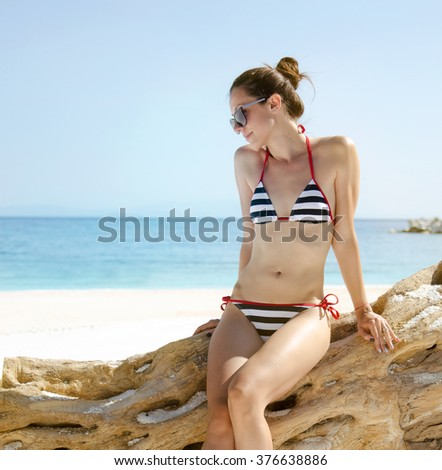Beautiful girl posing on the beach in a sunny day - stock photo
