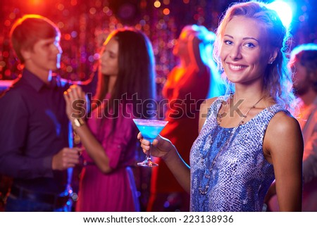 Beautiful girl posing with cocktail in nightclub, people dancing in the background