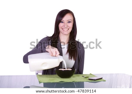 Beautiful Girl Pouring Milk to a Cereal Bowl with her cell phone on the table - Isolated