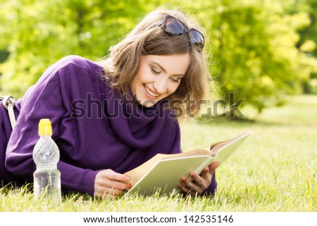 Beautiful girl reading a book and relax in the park