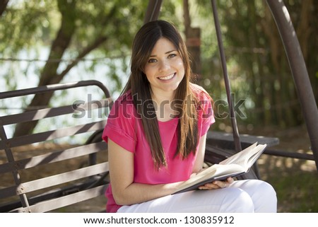 Beautiful girl reading a book and relaxing outdoors