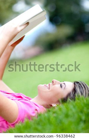 Beautiful girl reading a book outdoors and smiling