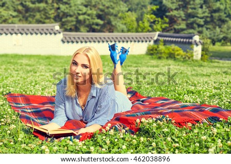 Beautiful girl reading book in the summer park. Portrait of young beautiful smiling woman on red cover outdoors. Beautiful young girl lying on the grass in the field.