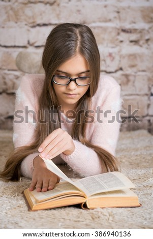 Beautiful girl reading book. Soft photo of girl with old book. education and school concept - little student girl studying and reading book at school. teen girl in glasses reading a book  - stock photo