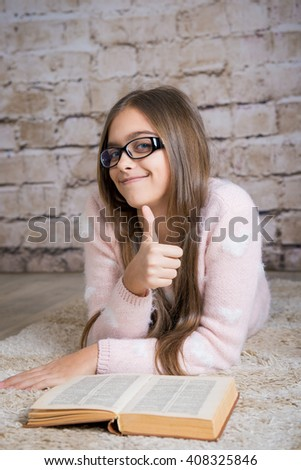 Beautiful girl reading book. Soft photo of girl with old book. education and school concept - little student girl studying and reading book at school. smart girl with glasses, girl with long hair - stock photo