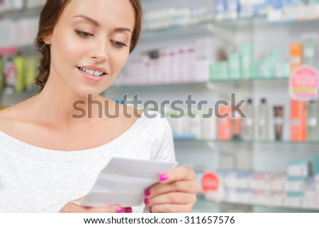 Beautiful girl reading instructions to the medicine in drugstore - stock photo