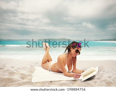 Beautiful girl reads a book on the beach - stock photo