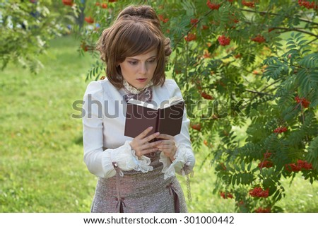 Beautiful girl reads book in the park                                - stock photo