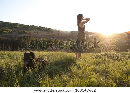 Beautiful girl relaxes in the sunlight whilst walking her dog - stock photo