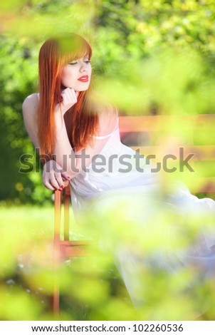 Beautiful girl relaxing in a magic garden - stock photo