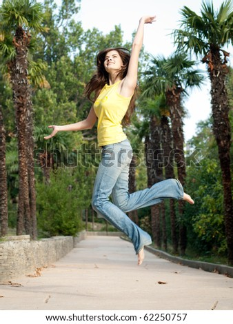 beautiful girl relaxing jumping outdoors in park - stock photo