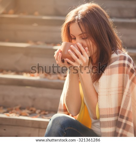Beautiful girl resting and drinking tea sitting in autumn garden on the steps, wrapped in a woolen plaid blanket.  - stock photo