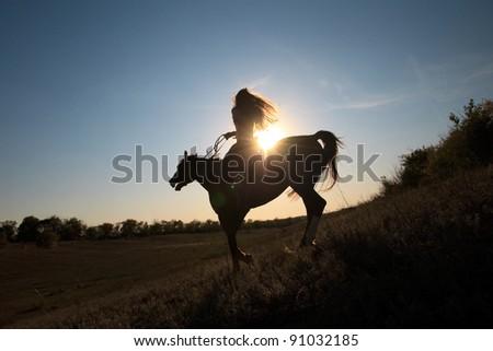 Beautiful girl  riding a horse against sun - stock photo