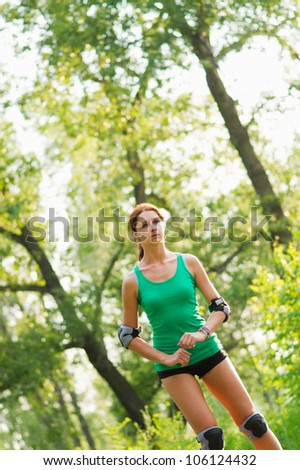 Beautiful girl rollerskating in park - stock photo