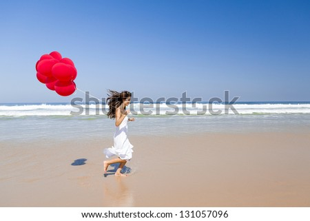 Beautiful girl running in the beach with red ballons in her hand - stock photo