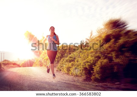 Beautiful girl running outdoors at sunset hour - stock photo